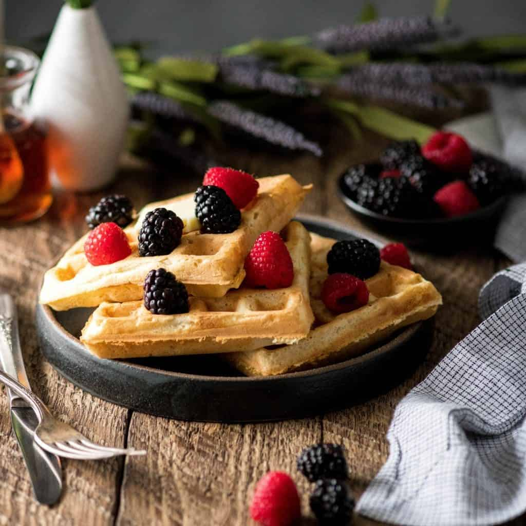 front view of three Best Waffles Recipe on a plate with berries on top