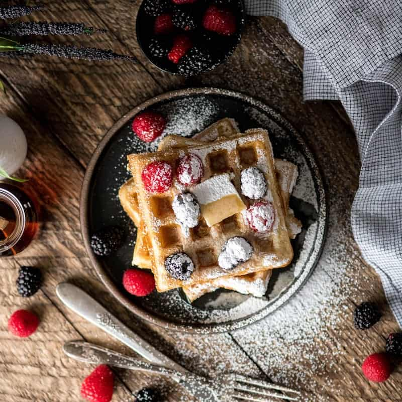 Overhead view of Best Waffles Recipe on a black plate with berries, syrup and powdered sugar