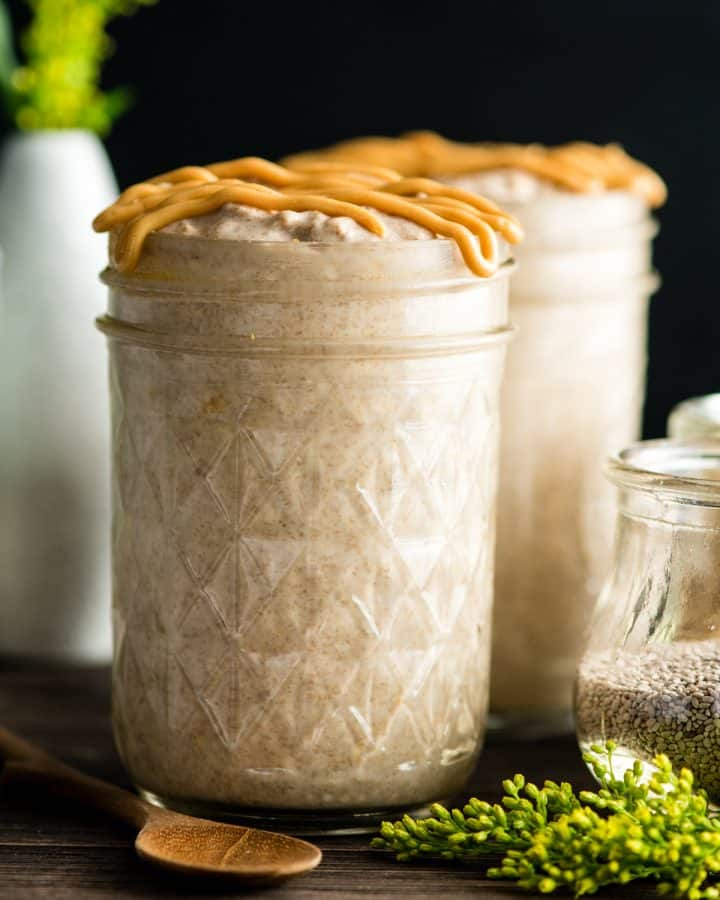 Front view of two jars of Peanut Butter Chia Overnight Oats with peanut butter drizzle