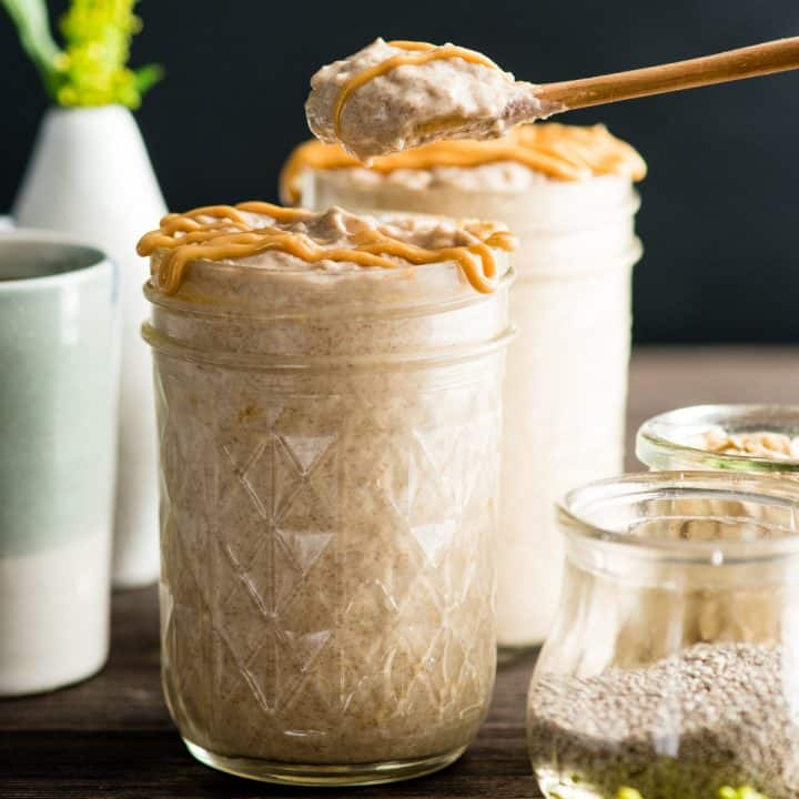 a spoon taking a bite out of a jar of Peanut Butter Overnight Oats