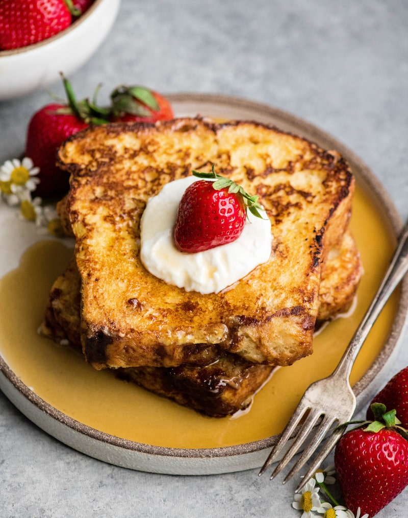 Overhead front view of two pieces of easy french toast stacked on each other with syrup, yogurt and berries