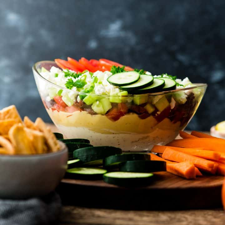 a bowl of layered Greek dip surrounded by veggies and pita chips