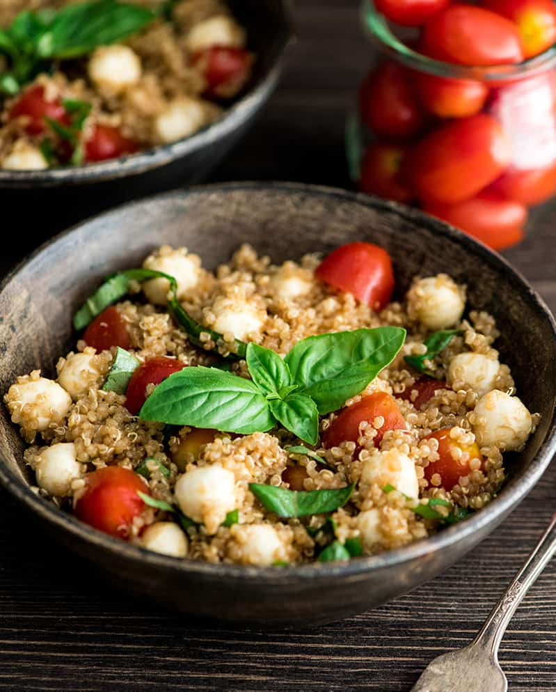 front view of a bowl of Balsamic Caprese Quinoa Salad garnished with fresh basil