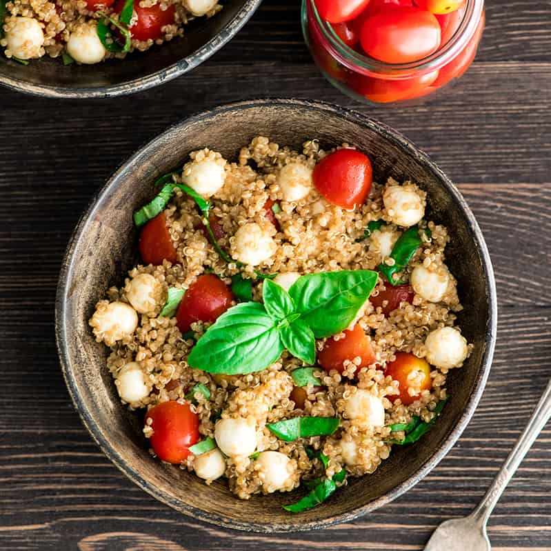 Overhead view of a bowl of Balsamic Caprese Quinoa Salad garnished with fresh basil