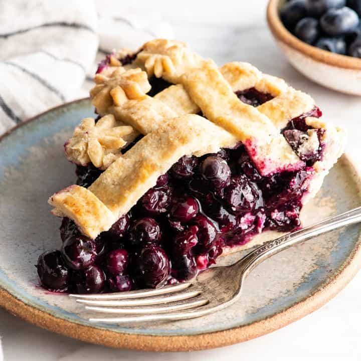 side view of a slice of blueberry pie on a plate