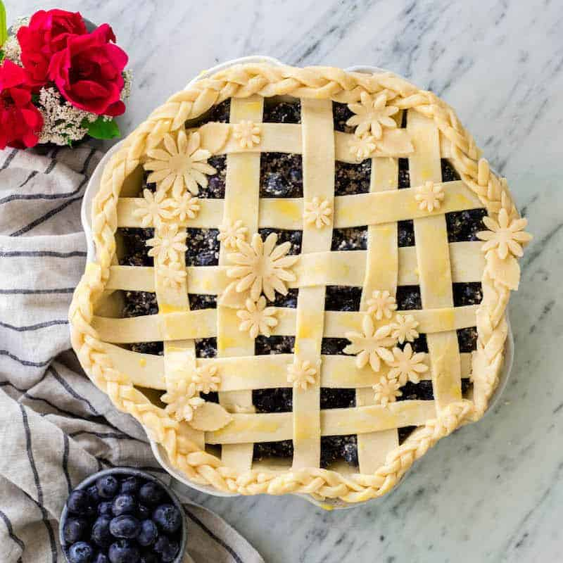 overhead view of Flaky Homemade All Butter Pie Crust arranged in a lattice with flowers on top of a blueberry pie before baking