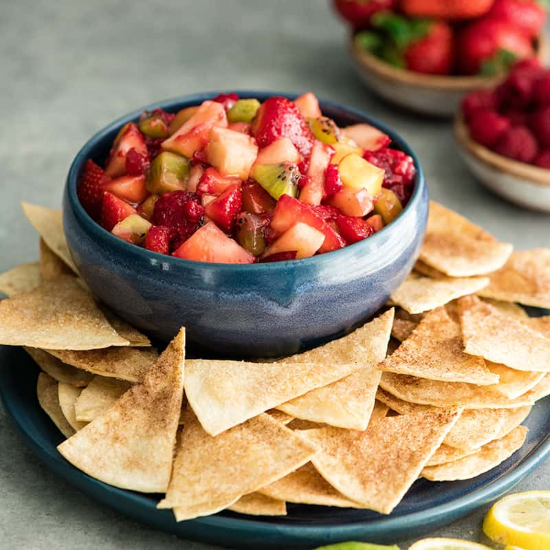 Front view of a bowl of Fruit Salsa Recipe with cinnamon chips on a serving plate