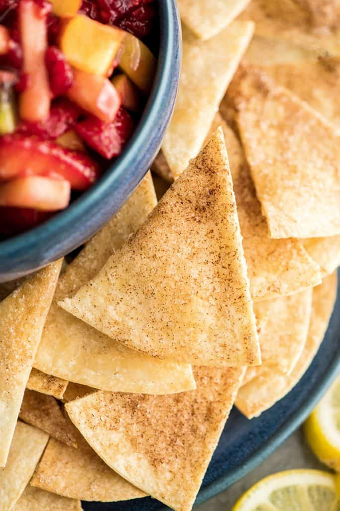 up close overhead view of a cinnamon chip next to a bowl of Fruit Salsa