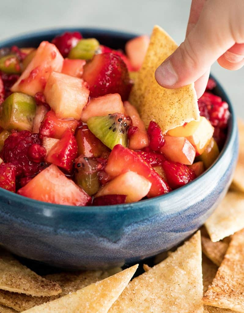 Up close, front view of a hand dipping a cinnamon chip into a bowl of fruit salsa