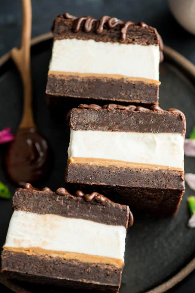 Up close overhead view of three Peanut Butter Brownie Ice Cream Sandwiches on a plate