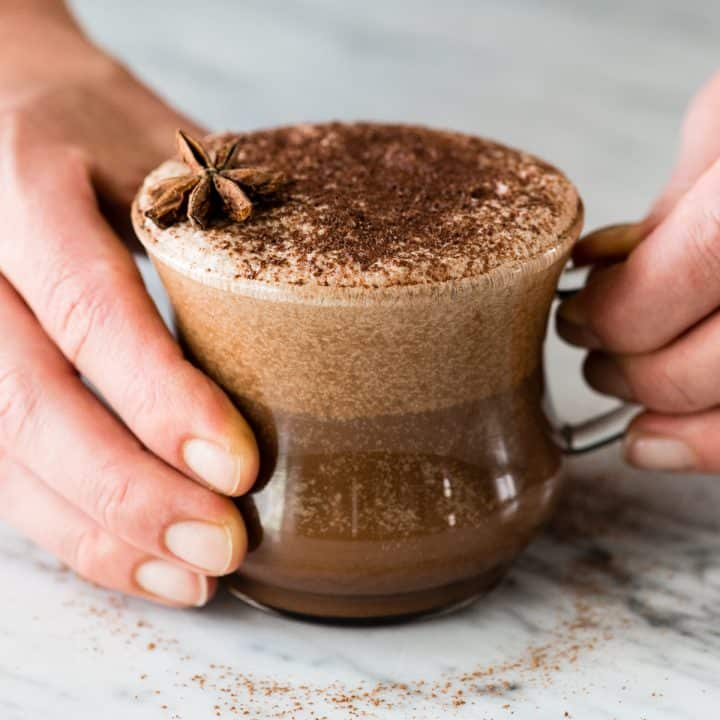 Front view of hands holding a glass mug filled with Dairy-Free Mocha Latte garnished with cocoa powder and star anise