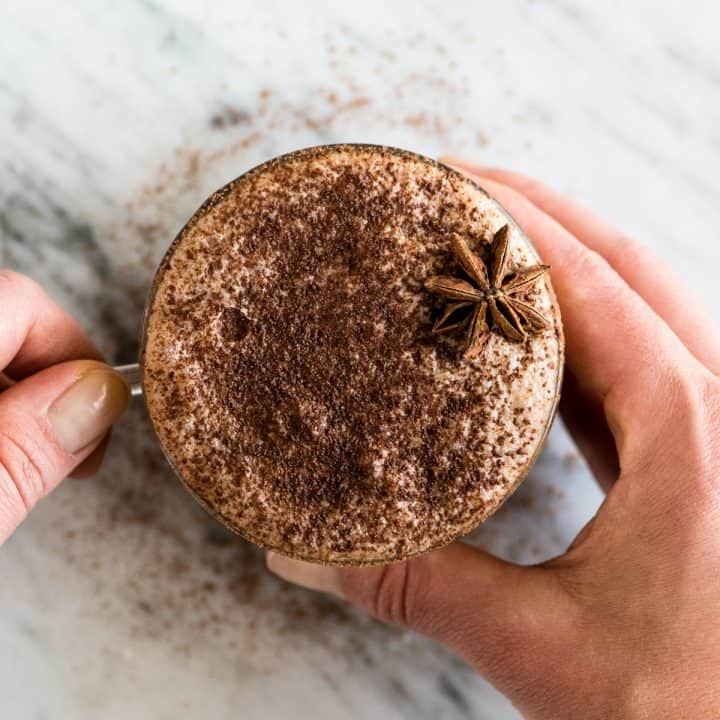 overhead view of hands holding a mug of Dairy-Free Mocha Latte