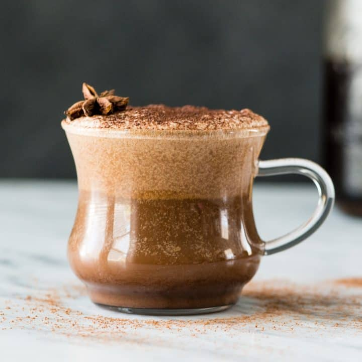 Front view of a glass mug filled with Dairy-Free Mocha Latte garnished with cocoa powder and star anise