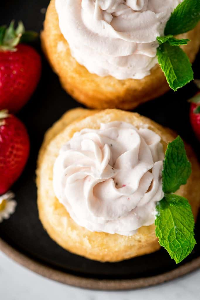 Up close, overhead view of two sponge cakes with Strawberry Whipped Cream piped on top of them, garnished with fresh mint