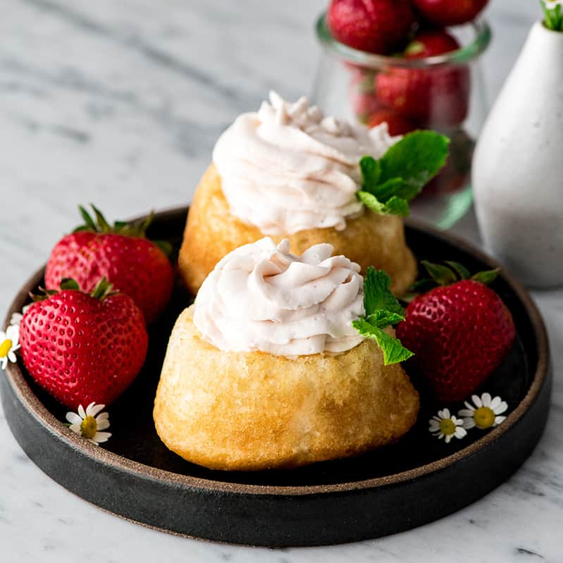 Front view of two sponge cakes with Strawberry Whipped Cream piped on top of them, garnished with fresh mint