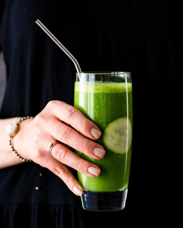 Front view of a hand holding a Zucchini Smoothie