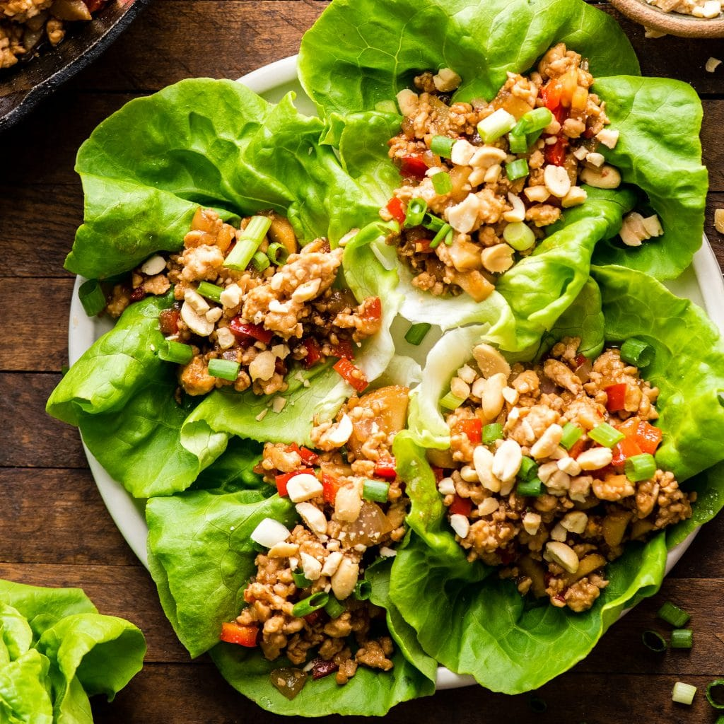 overhead view of four chicken lettuce wraps on a plate