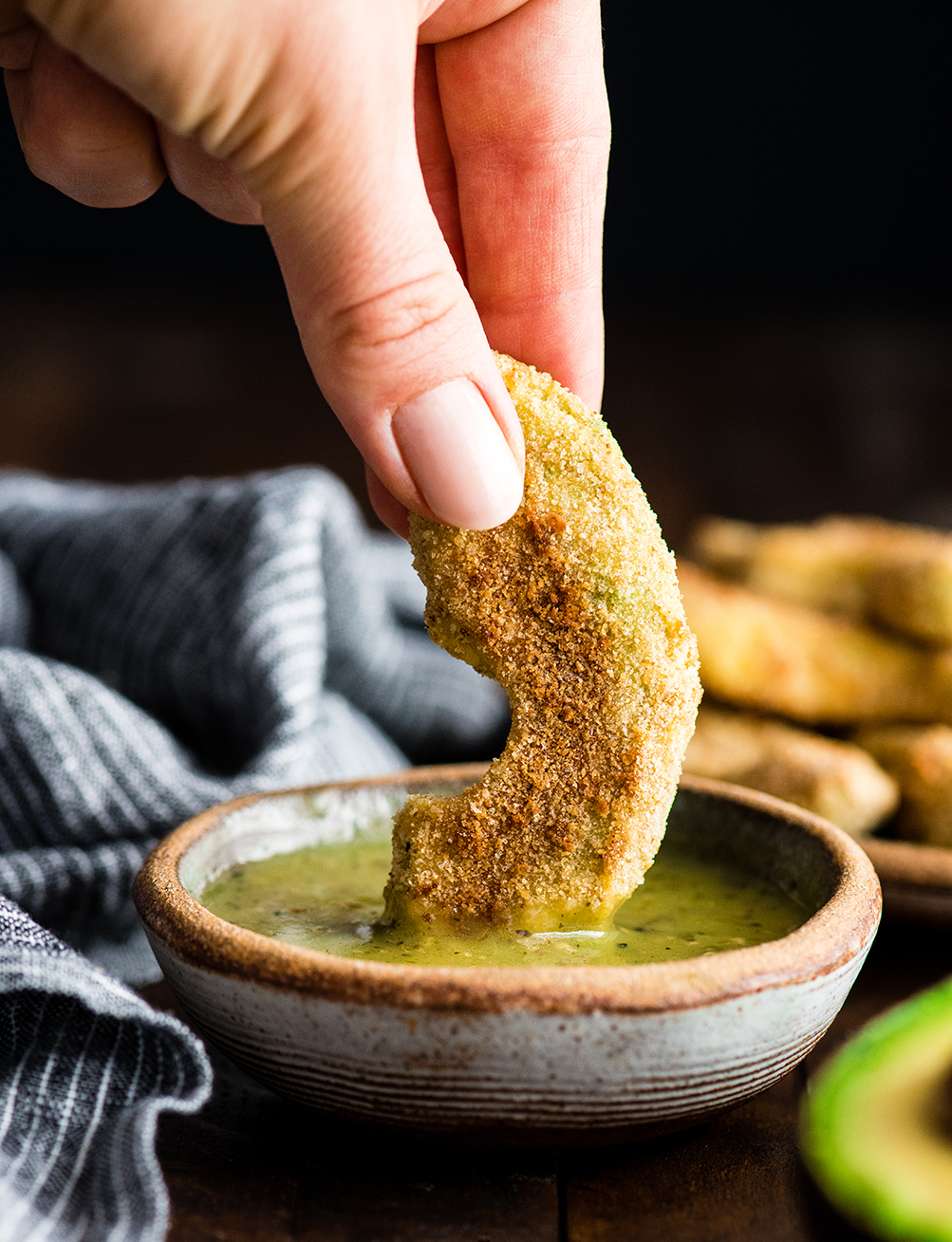 Front view of a hand dipping a Baked Avocado Fry in dipping sauce