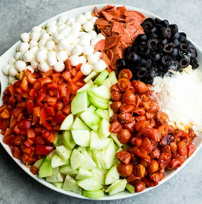 overhead view of the best pasta salad recipe in a large white serving bowl with all the ingredients organized separately before being mixed together