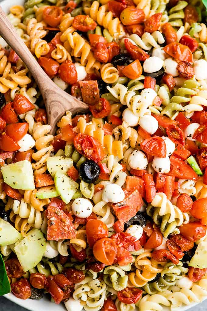 overhead view of the best pasta salad recipe in a large white serving bowl with a wooden spoon taking a scoop