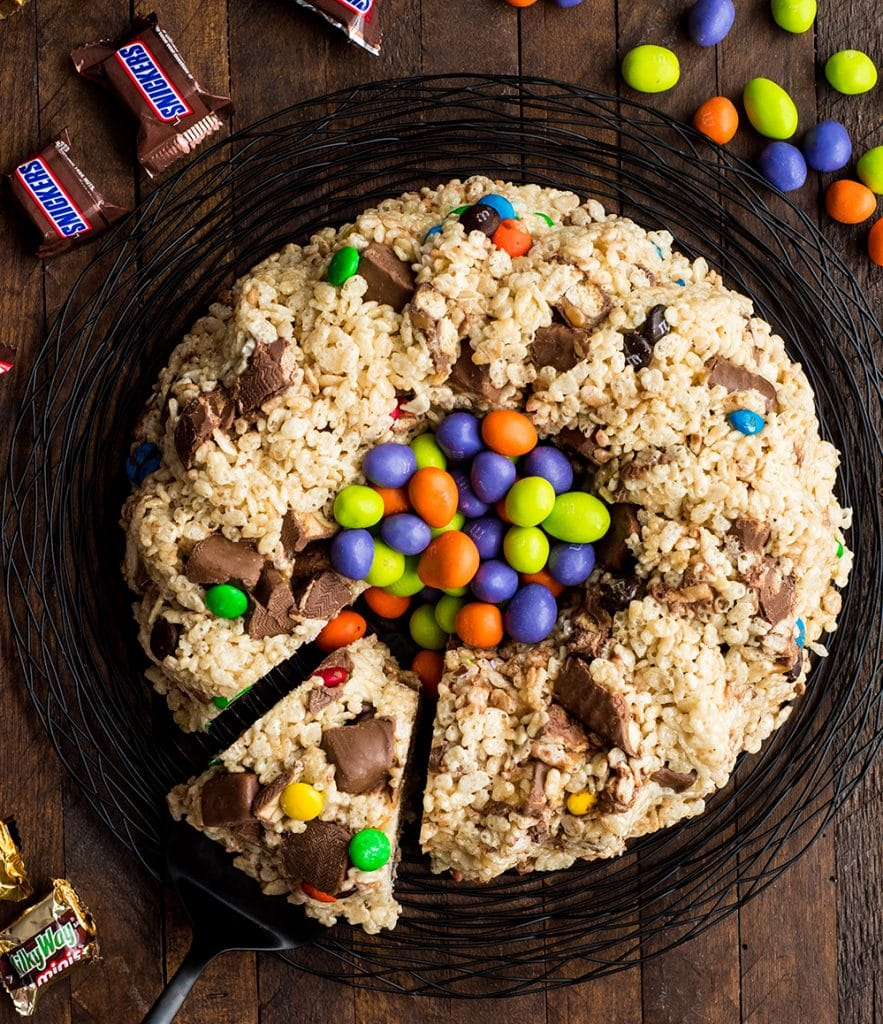 Overhead view of Candy-Stuffed Rice Crispy Cake filled with M&Ms with one piece of the cake cut and being pulled out with a cake server