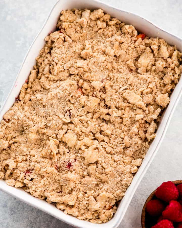 Overhead view of raspberry peach crisp in a baking dish before being put in the oven.