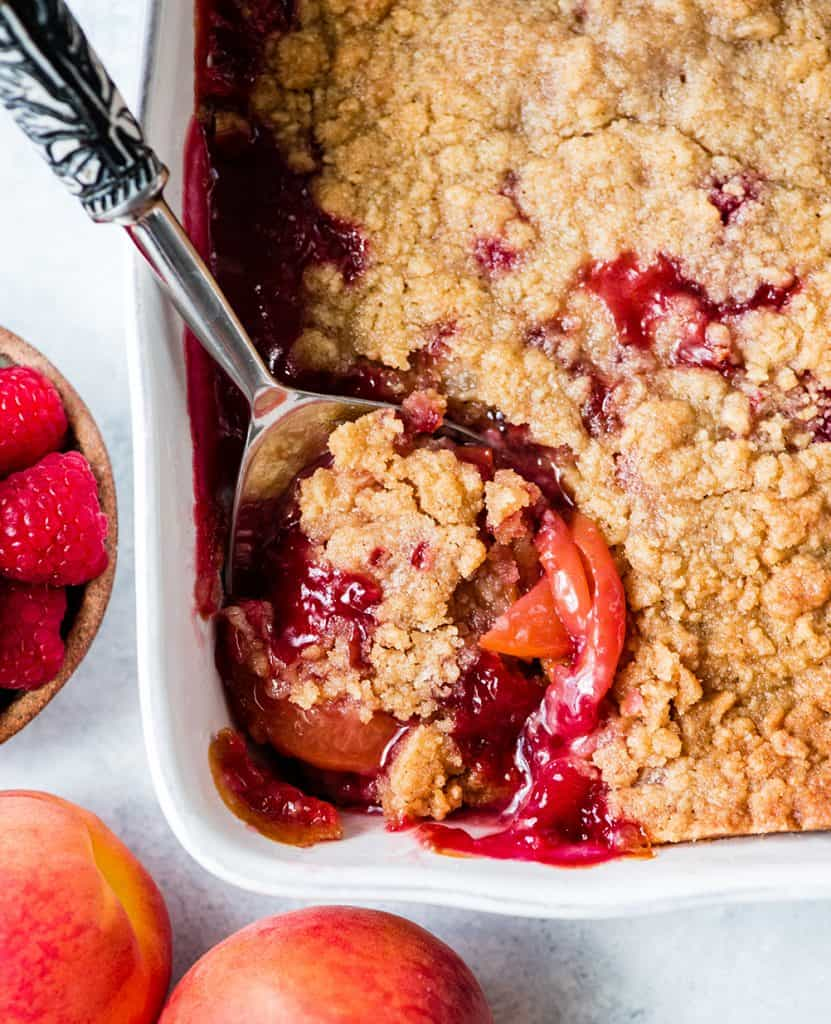 Close-up overhead view of a spoon taking a scoop of Raspberry Peach Crisp out of the baking dish