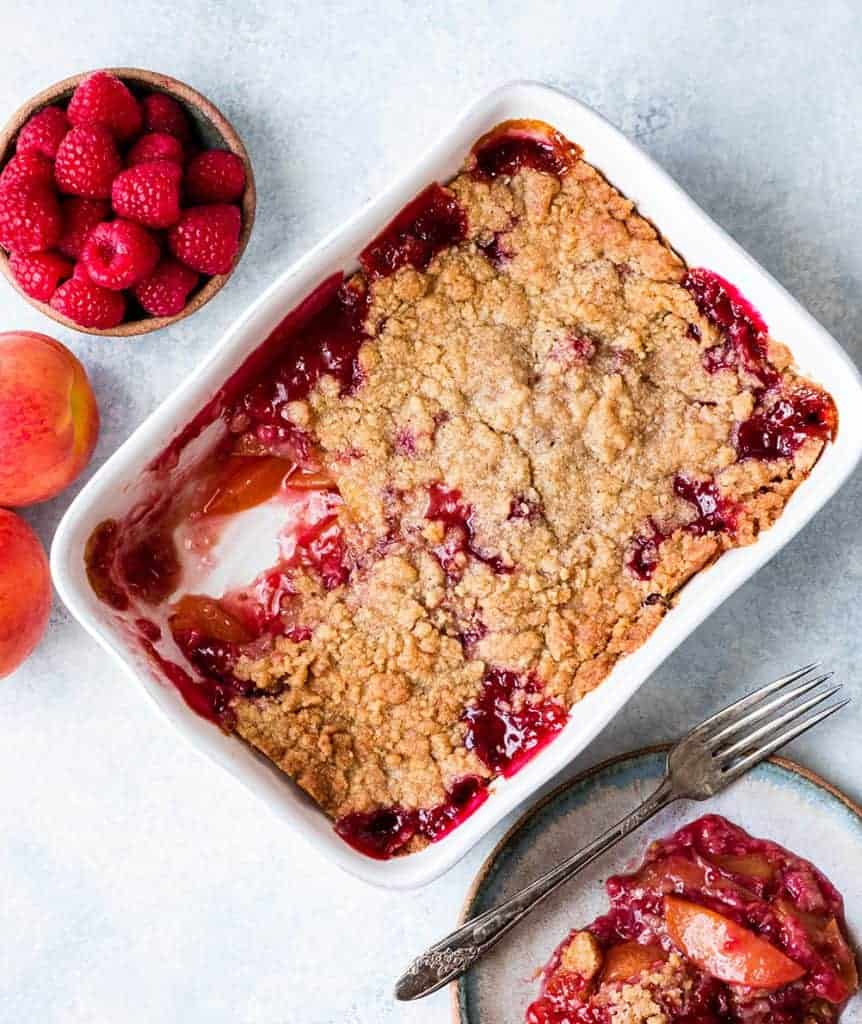 Overhead view of a Raspberry Peach Crisp in a baking dish with a serving scooped out on a plate nearby