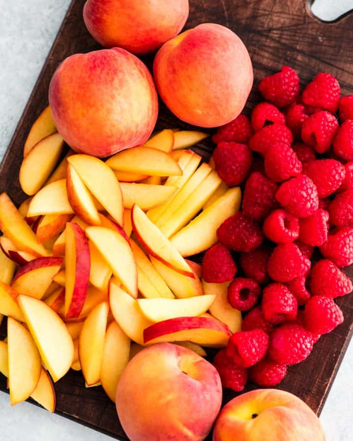 Overhead view of slices peaches and full raspberries on a cutting board in the making of Raspberry Peach Crisp