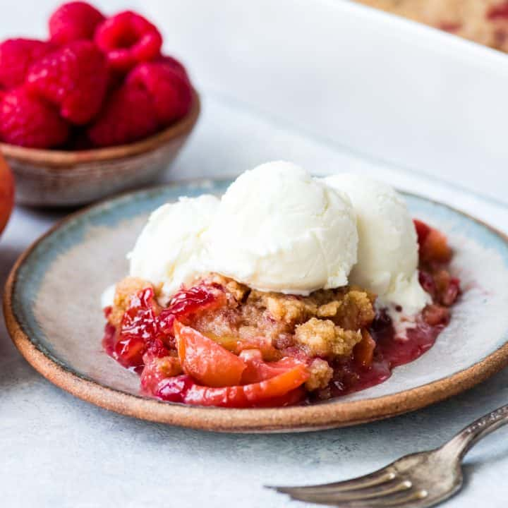 front view of a serving of Raspberry Peach Crisp on a plate topped with vanilla ice cream