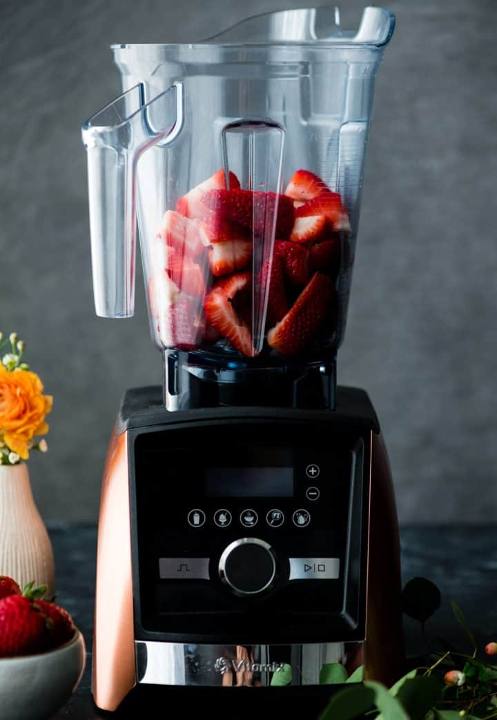 Front view of strawberries in a vitamix blender ready to be made into this Strawberry Sauce recipe