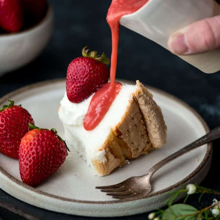 overhead/front view of Strawberry Sauce being poured onto a piece of angel food cake