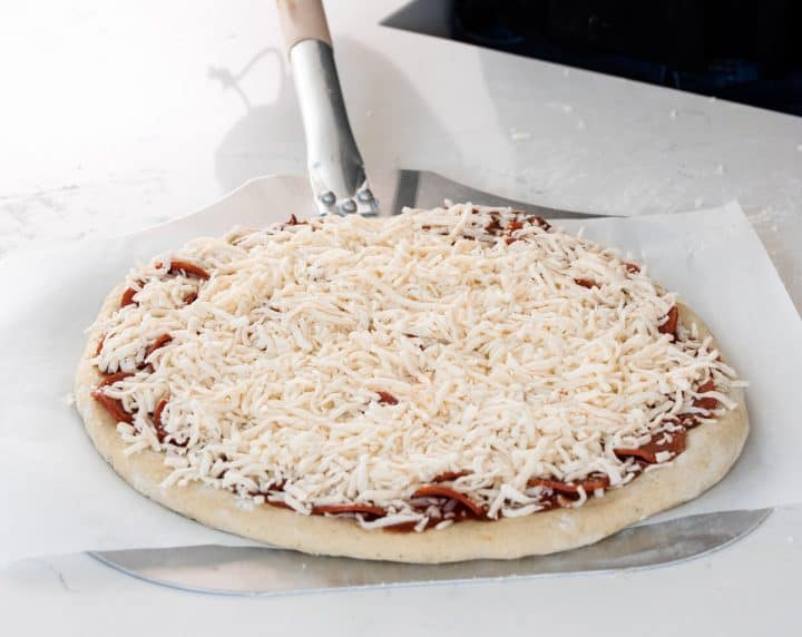 photo showing How to Make Pizza Dough - assembled pizza on a pizza peel ready to go into the oven