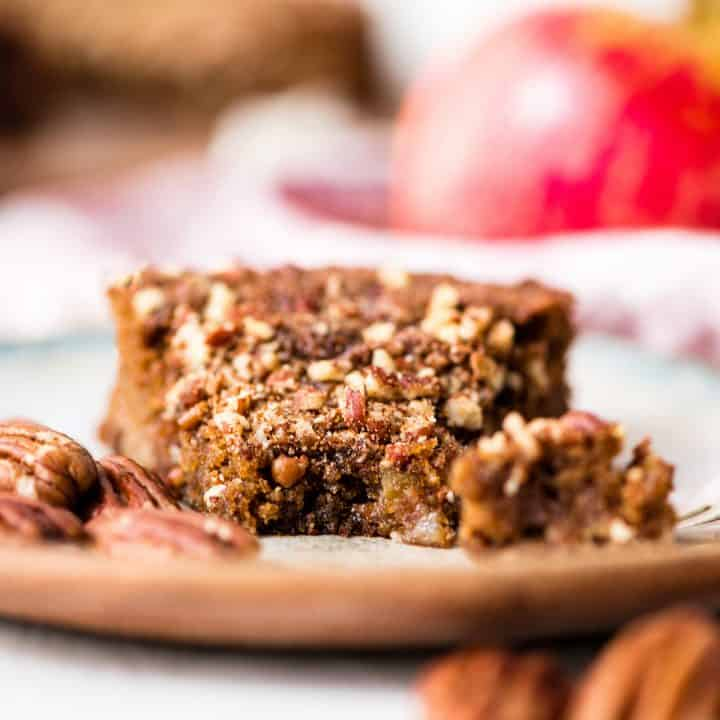 Front view of a piece of paleo gluten-free apple cake on a plate with a bite taken out of it