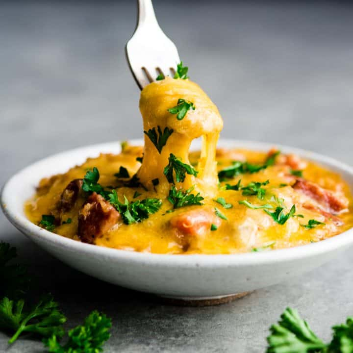 front view of a fork lifting a bite of Baked Quinoa Casserole out of a bowl showing a stringy cheese pull topped with fresh parsley