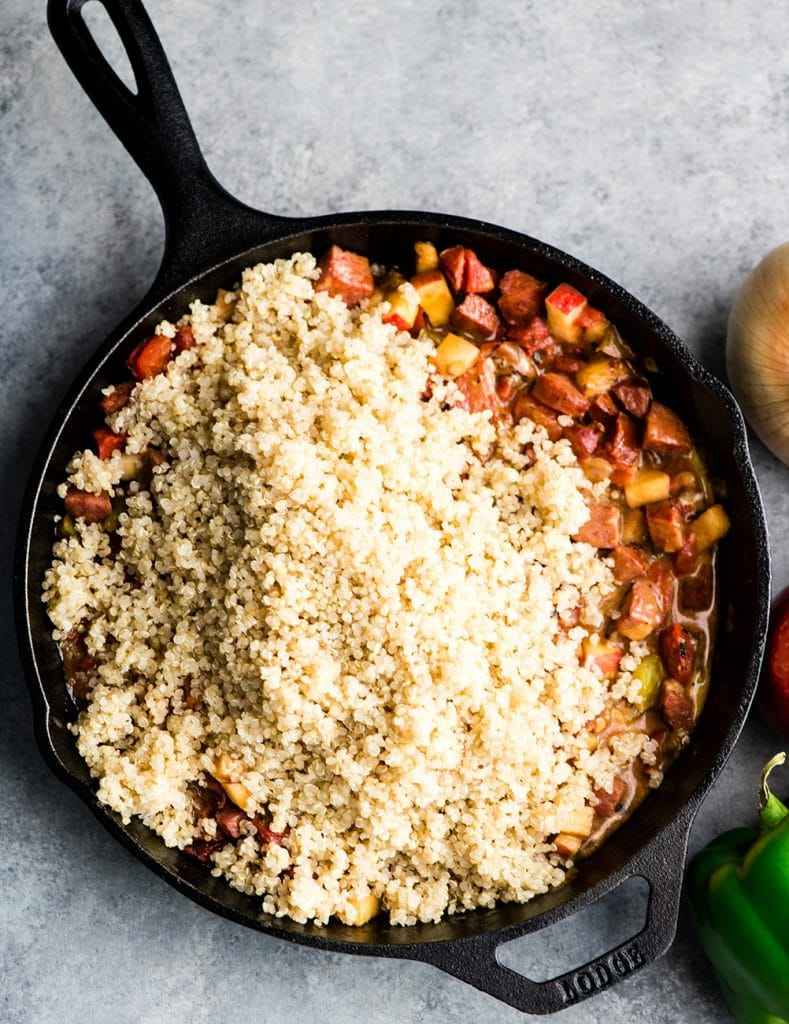 Overhead view of a cast iron skillet after the cooked quinoa has been added in the making of this Baked Quinoa Casserole recipe
