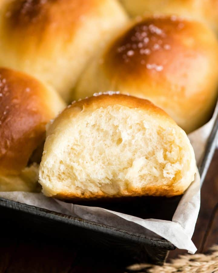 up close overhead view of a Homemade Dinner Roll in the pan with other rolls surrounding it after baking