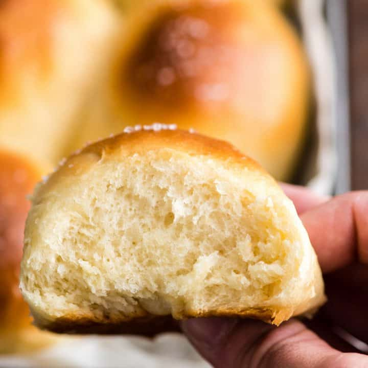 front view of a hand removing one Best Homemade Dinner Rolls from the pan