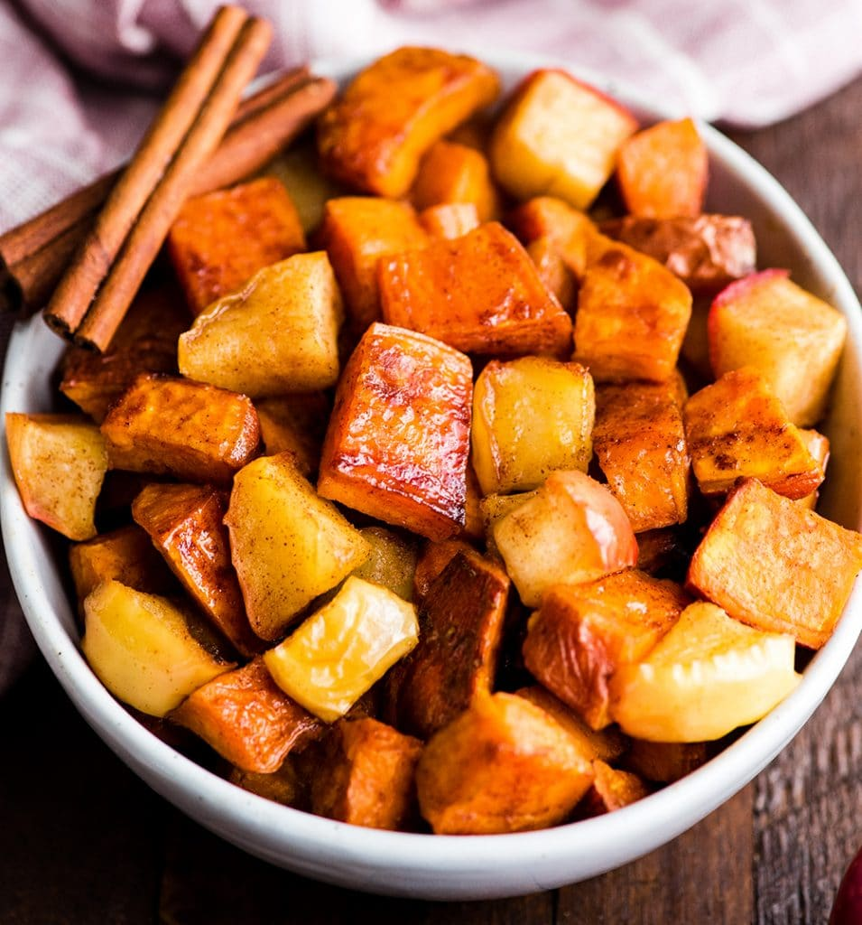 up close front view of a bowl of cinnamon roasted sweet potatoes and apples ready to be served
