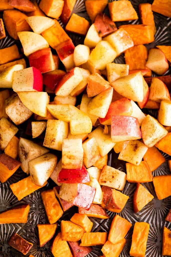 close-up overhead view of apples and sweet potatoes on a baking sheet tossed with cinnamon before baking the final time in this Cinnamon Roasted Sweet Potatoes and Apples recipe
