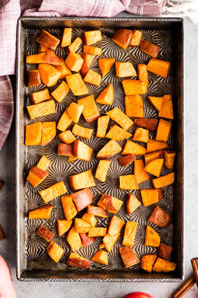 overhead view of a pan of sweet potatoes roasted alone which is the first step in making this Cinnamon Roasted Sweet Potatoes and Apples recipe