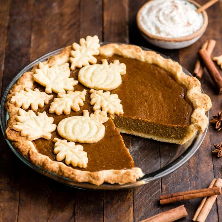 overhead front view of a dairy-free pumpkin pie in a glass pie dish with one slice removed