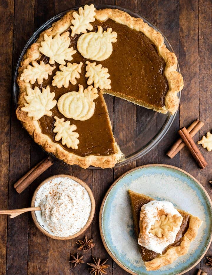 overhead view of dairy-free pumpkin pie in a glass pie dish with one piece cut out and on a plate next to the pie dish