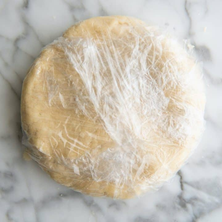 dairy free pie crust wrapped in plastic wrap to chill