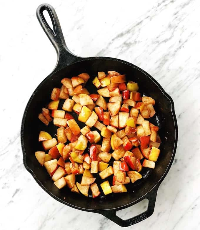 overhead view of cinnamon sautéed apples being cooked in a cast iron skillet