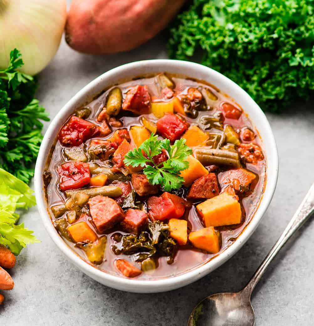Overhead view of a bowl of Sausage Kale Soup topped with parsley