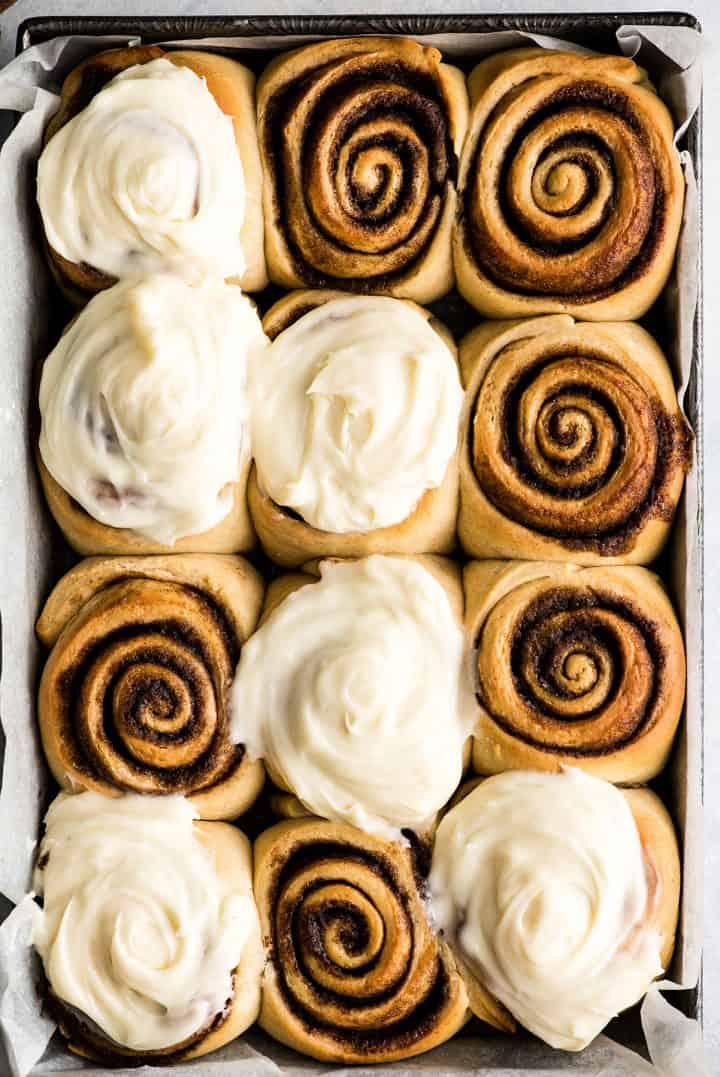 overhead view of a pan of 12 homemade cinnamon rolls with cream cheese frosting