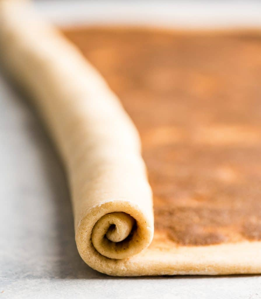 Front view of the best cinnamon rolls recipe dough being rolled up (halfway through the process)
