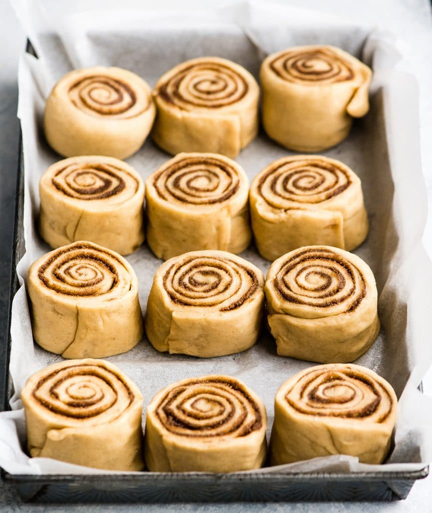 front/overhead view of 12 best cinnamon rolls in a baking sheet lined with parchment paper before the second rise