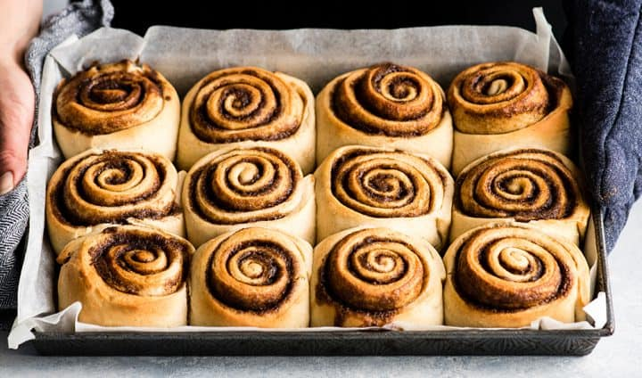 front photo of hands holding a pan of baked cinnamon rolls